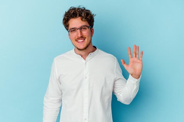 Junger geschäftsmann lokalisiert auf der blauen wand, die fröhlich lächelnd zeigt nummer fünf mit den fingern