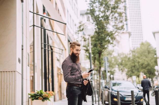 Junger geschäftsmann macht sich auf den weg zur arbeit und schaut ins telefon.