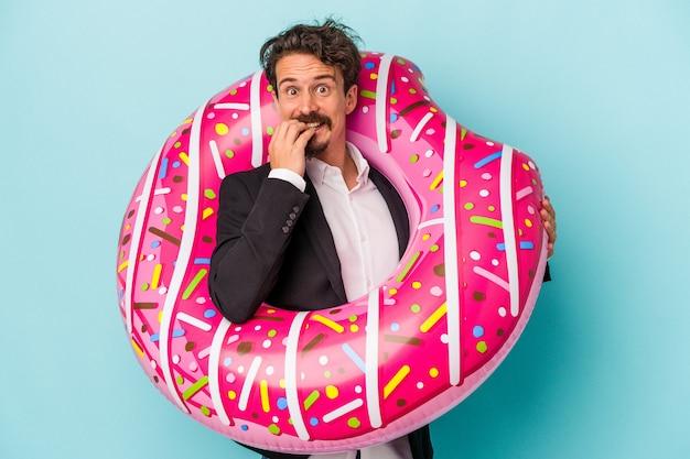 Junger geschäftsmann mit aufblasbarem donut einzeln auf blauem hintergrund beißende fingernägel, nervös und sehr ängstlich.