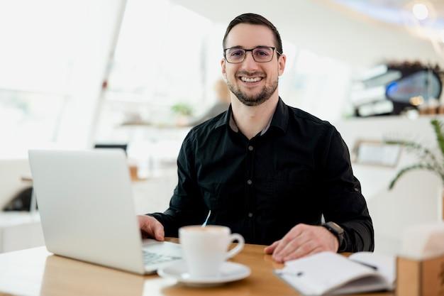 Junger geschäftsmann mit brille, der kaffee trinkt, während er am laptop im kaffeehaus arbeitet, männlicher freiberufler, der text auf der laptop-tastatur schreibt, während er eine tasse cappuccino in einem modernen café genießt.