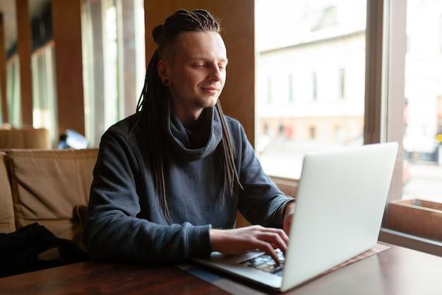 Junger geschäftsmann mit dem dreadlock, der seine arbeit im café mit laptop erledigt.