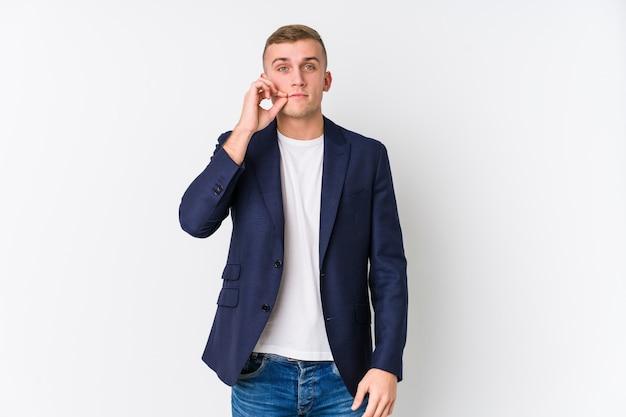 Junger geschäftsmann mit den fingern auf den lippen, die ein geheimnis halten