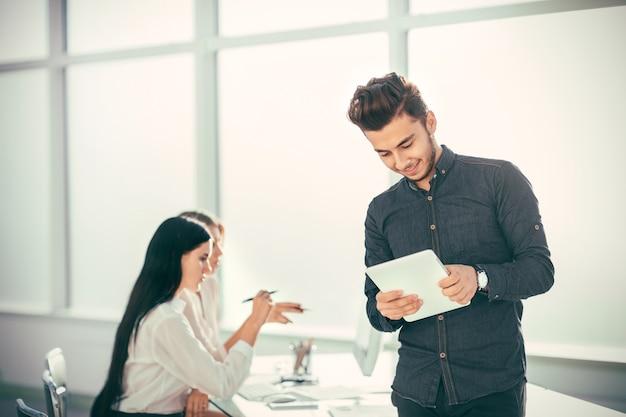 Junger geschäftsmann mit digitaler tablette, die im büro steht. foto mit textfreiraum