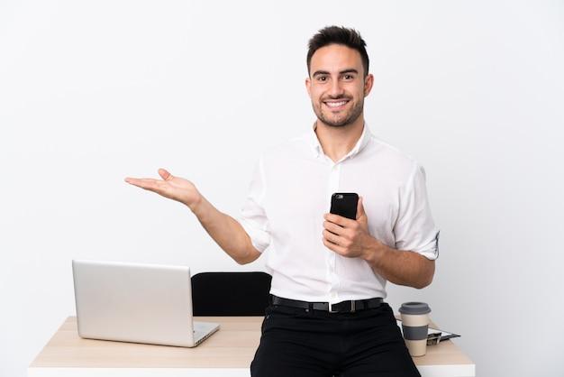 Junger geschäftsmann mit einem handy an einem arbeitsplatz, der copyspace eingebildet auf der palme hält