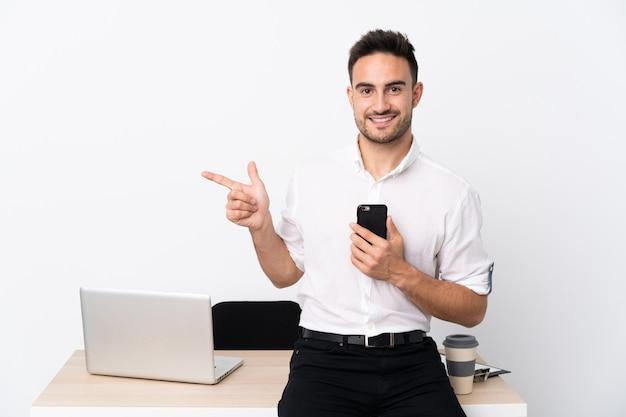 Junger geschäftsmann mit einem handy an einem arbeitsplatz finger auf die seite zeigend