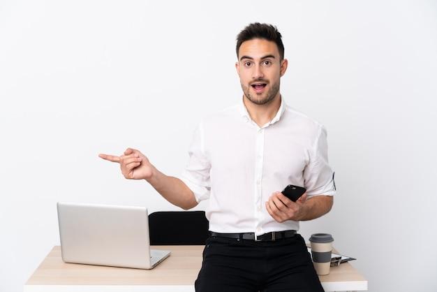 Junger geschäftsmann mit einem mobiltelefon an einem arbeitsplatz überrascht und zeigt finger zur seite