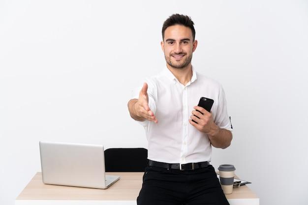 Junger geschäftsmann mit einem mobiltelefon in einem arbeitsplatz händeschütteln nach vielem