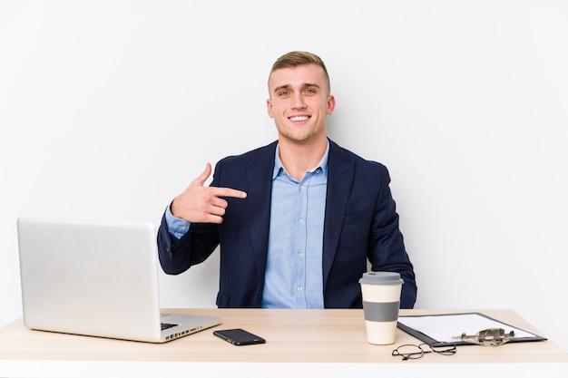 Junger geschäftsmann mit einer laptop-person, die von hand auf eine leere stelle des hemdes zeigt, stolz und zuversichtlich