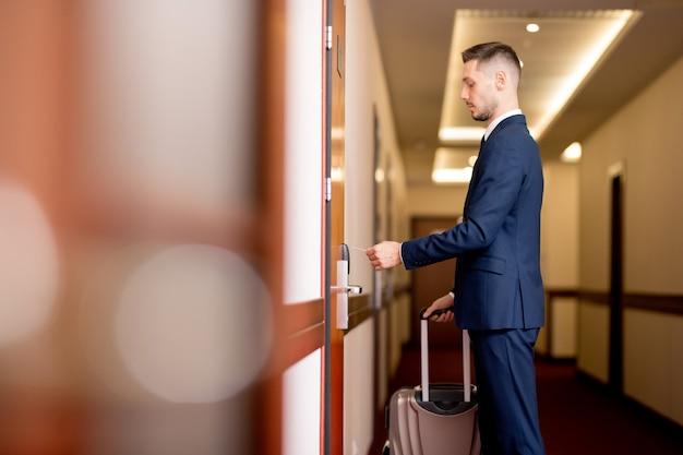 Junger geschäftsmann mit gepäck, das plastikkarte durch tür hält, während er den raum nach ankunft im hotel betritt