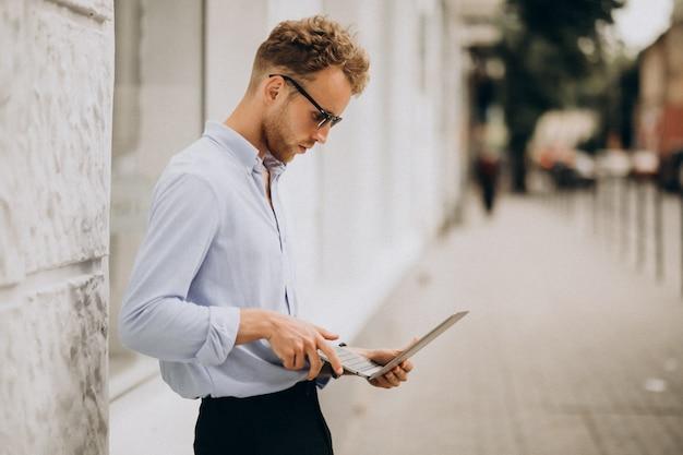 Junger geschäftsmann mit laptop draußen in der stadt