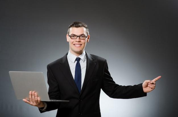 Junger geschäftsmann mit laptop im geschäftskonzept