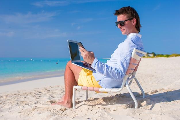 Junger geschäftsmann mit laptop und telefon am tropischen strand