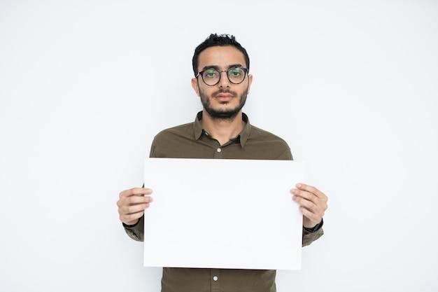 Junger geschäftsmann mit leerem gesicht, das leeres plakat in der isolation hält