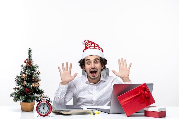 Junger geschäftsmann mit lustigem weihnachtsmannhut, der über die nachrichten, die er im büro hört, schockiert ist