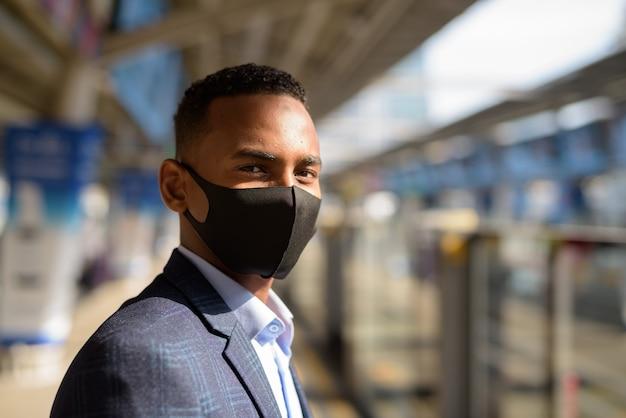 Junger geschäftsmann mit maske zum schutz vor dem ausbruch des koronavirus, der am himmelbahnhof wartet