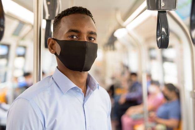 Junger geschäftsmann mit maske zum schutz vor dem ausbruch des koronavirus, der mit abstand innerhalb des zuges steht