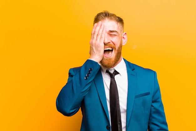 Junger geschäftsmann mit rotem kopf, der schläfrig, gelangweilt und gähnend aussieht, mit kopfschmerzen und einer hand, die das halbe gesicht gegen die orange wand bedeckt