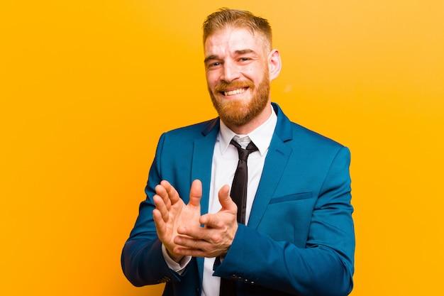 Junger geschäftsmann mit rotem kopf, der sich glücklich und erfolgreich fühlt, lächelt und in die hände klatscht und glückwünsche mit einem applaus über der orangefarbenen wand sagt