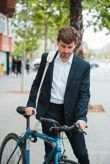 Junger geschäftsmann mit seinem rucksack, der mit fahrrad auf straße steht