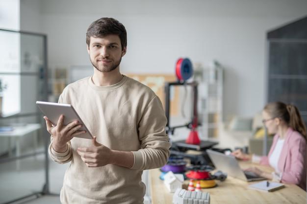 Junger geschäftsmann mit touchpad stehend mit kollege, der mit 3d-drucker arbeitet