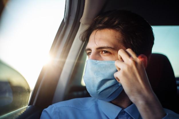 Junger geschäftsmann nimmt ein taxi und schaut aus dem autofenster, das sterile medizinische maske justiert. soziales distanzkonzept.