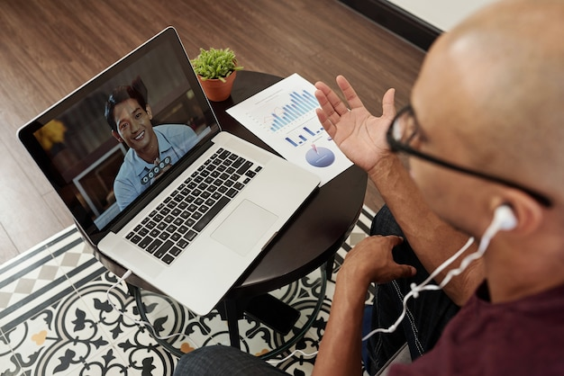 Junger geschäftsmann sitzt am kleinen tisch mit finanzbericht und video, das seinen vietnamesischen kollegen anruft