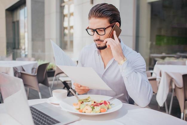 Junger geschäftsmann sitzt am tisch im restaurant und spricht am telefon. er schaut auf den bildschirm des laptops. es gibt eine schüssel salat und eine tasse kaffee am tisch.