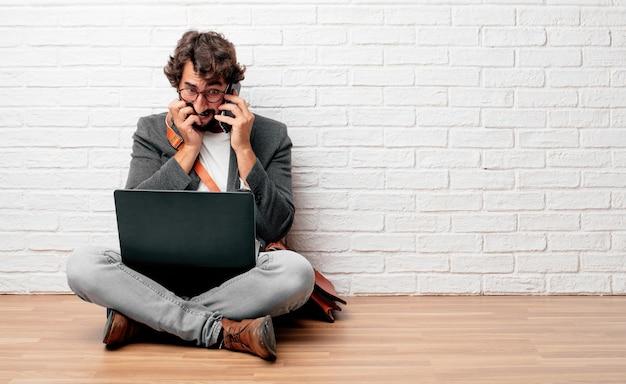 Junger geschäftsmann sitzt auf dem boden mit einem laptop