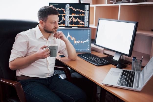 Junger geschäftsmann sitzt im büro am tisch und arbeitet am computer mit vielen monitoren, diagrammen auf dem monitor. börsenmakler analysiert binäre optionsdiagramme. hippster-mann, der kaffee trinkt, studiert.