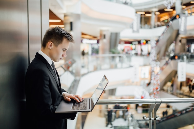 Junger geschäftsmann steuert geschäft auf laptop, innen-, profilansicht, gekleidet im schwarzen anzug im einkaufszentrum,