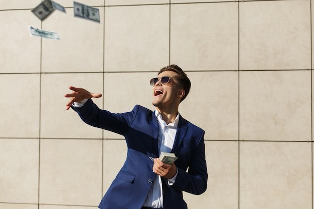 Junger geschäftsmann throughs um dollar und tänze auf der straße