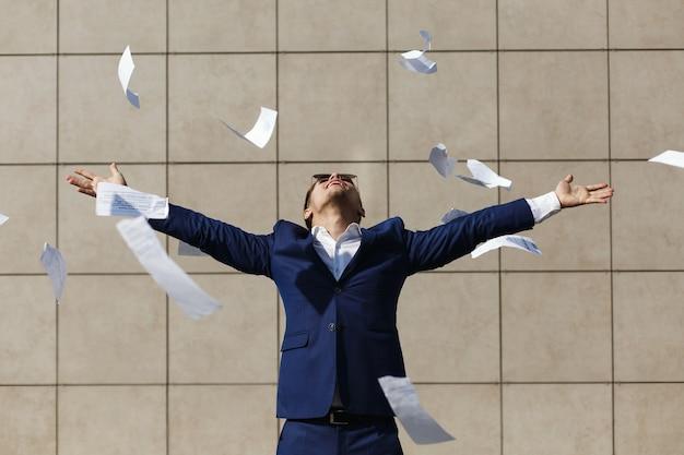 Junger geschäftsmann throughs weg die papiere, die auf der straße stehen