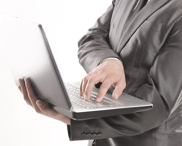 Junger geschäftsmann tippt auf laptop.isolated on white