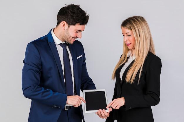 Junger geschäftsmann und geschäftsfrau, die seinen finger auf digitaler tablette gegen grauen hintergrund zeigt