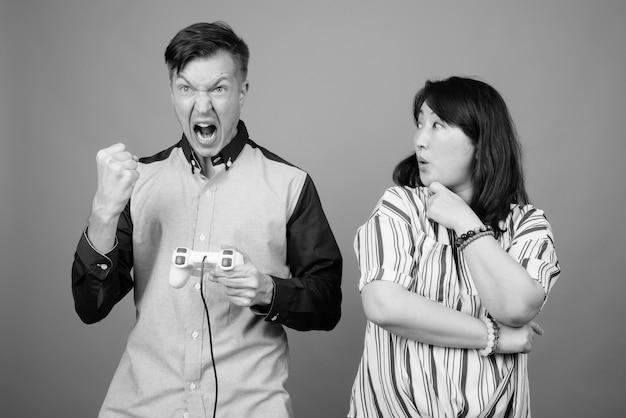 Junger geschäftsmann und reife japanische geschäftsfrau zusammen gegen grau in schwarzweiss