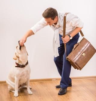 Junger geschäftsmann zieht seinen reizenden hund ein.