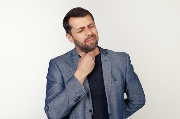 Junger geschäftsmannmann mit bart, der schmerzhaften hals, halsschmerzen von grippe, klumpen und infektion berührt.