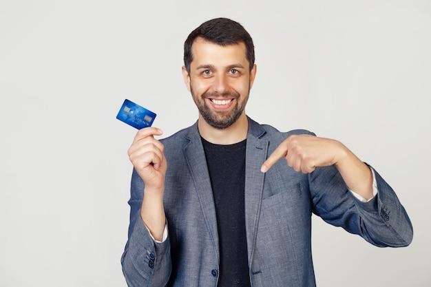 Junger geschäftsmannmann mit bart in der jacke, die kreditkarte hält, die auf lokalisiertem weißem hintergrund steht