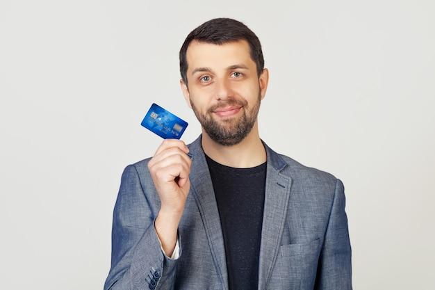 Junger geschäftsmannmann mit einem bart in einer jacke, die eine kreditkarte mit einem selbstbewussten ausdruck auf einem klugen gesicht hält und ernsthaft denkt.