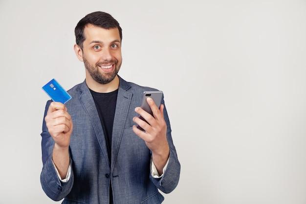 Junger geschäftsmannmann mit einem bart in einer jacke, hübscher mann, der eine kreditkarte verwendet, um online mit einem smartphone zu bezahlen.