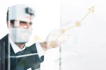 Junger Geschäftsmann, der Finger auf zunehmendes Diagramm auf transparentem Glas zeigt