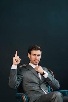Junger Geschäftsmann, der im Lehnsessel zeigt Hand mit einem Finger oben sitzt