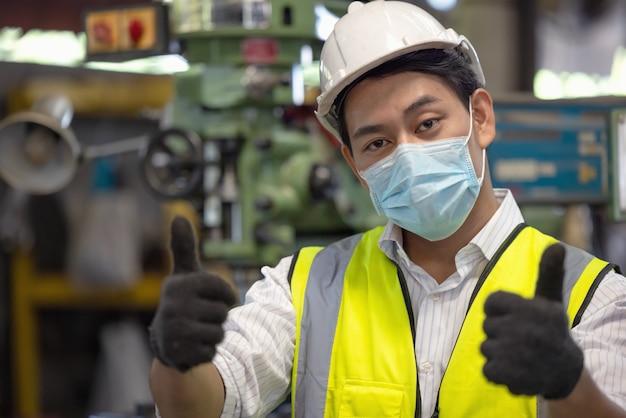 Junger geschickter fabrikarbeiter oder ingenieur schließen porträt in der fabrik