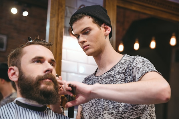 Junger geschickter friseur, der einem gutaussehenden bärtigen mann im friseursalon haarschnitt macht