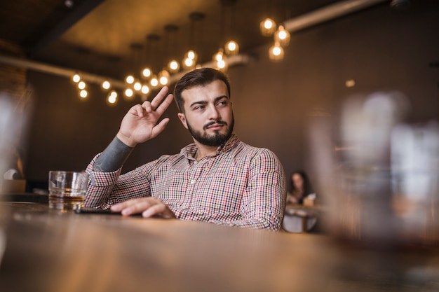 Junger gestikulierender mann beim trinken des alkohols an der stange