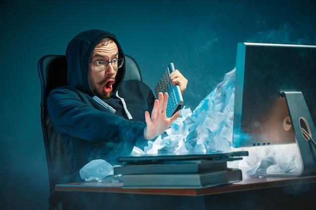 Junger gestresster gutaussehender geschäftsmann, der am schreibtisch im modernen büro arbeitet und laptop-bildschirm schreit und über spam wütend ist