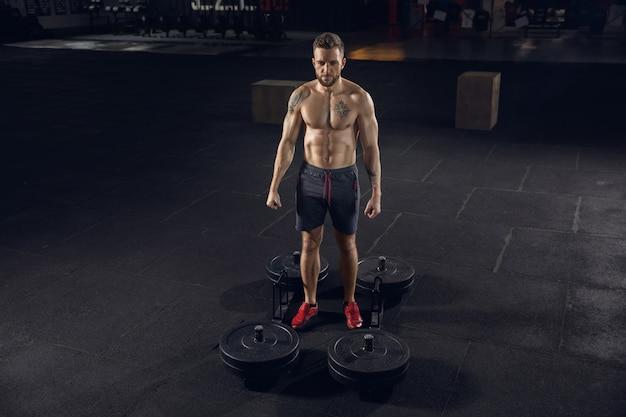 Junger gesunder männlicher athlet, der übungen im fitnessstudio macht