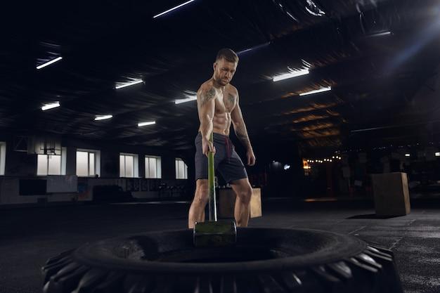 Junger gesunder mann, athlet, der ausgleichsübungen im fitnessstudio macht