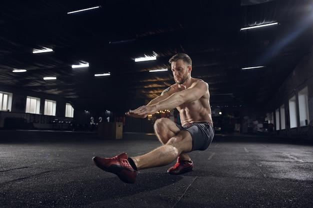Junger gesunder mann, athlet, der gleichgewichtsübungen macht, kniebeugen im fitnessstudio. einzelne model übt hart und trainiert seinen unterkörper. konzept des gesunden lebensstils, des sports, der fitness, des bodybuildings, des wohlbefindens.