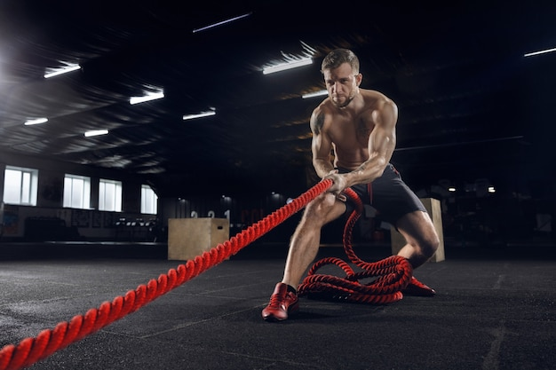 Junger gesunder mann, athlet, der übung mit den seilen im fitnessstudio tut